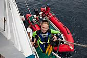 Diver enters Liveabord after Diving, Raja Ampat, West Papua, Indonesia