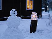 Snowman and snowball lantern in garden