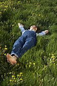 Girl lying on the meadow with dandelions