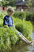 Boy is splashing with his feet in a stream