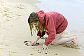Girl puts stones as a heart on the beach
