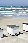 Man reads, leaning on a white bathing huts on the beach, Jutland, Denmark