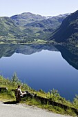 Man reads a book and have a beautiful view over lake and mountains, the Roldals water (Roldalsvattnet), Norway