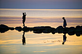 Silhouettes of children playing on a stonewall in the sea
