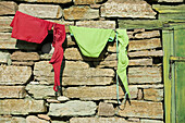 Red and green bikini hangs out to dry on stone hut