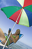Woman under a brightly-coloured umbrella