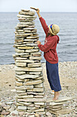 Girl in straw hat and sunglasses is building a stone tower