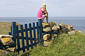 Girl with straw hat is sitting on a blue fence at the sea