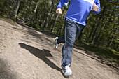 Man runs in Kronoskogen, Ängelholm, on a fitness path, Skåne, Sweden