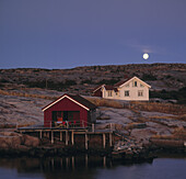 Full moon over house and fishing hut in Bohuslan archipelago, Sweden