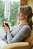 Woman relaxing in chair and is drinking tea