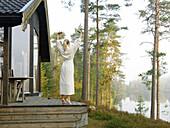 Woman in robe on terrace, Skane, Sweden