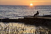 Woman on pier enjoying the sunset