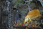 Sitting Buddha with yellow scarf and incense sticks at Wat Phu Champasak, Khmer temple, Southern Laos, Asia