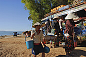 Women vendors selling food to bus passengers waiting for ferry, Champasak, Southern Laos, Asia