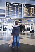 Boy with teddy bear in terminal, Munich airport, Bavaria, Germany