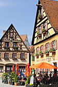 Guests sitting in the beer garden of a restaurant, half-timbered houses, Dinkelbuehl, Bavaria, Germany