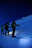 Three men backcountry skiing at night, ascent to hut Staufner Haus at Hochgrat with view to Hochgrat, Hochgrat, Nagelfluh range, Allgaeuer Alpen range, Allgaeu, Bavaria, Germany