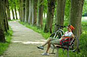 Female cyclist resting on bench in lime tree alley, Altmuehltal cycle trail, Altmuehltal natural park, Altmuehltal, Bavaria, Germany
