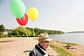 Senior man in a wheelchair with balloons at lake Kulkwitzer See, Leipzig, Saxony, Germany