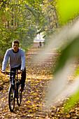 Cyclist in autumn wood, Rosental, Leipzig, Saxony, Germany