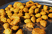 Fried zucchini balls displayed at a food stand in the zouk, Abu Simbel, Egypt, Africa