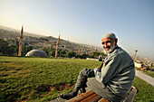 Older man sits on a bench, view on Sanliurfa, southeast-Anatolia, Turkey