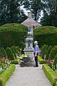 Gardener pushing a wheelbarrow in the castle gardens, trimmed hedges in the castle grounds of Clemenswerth Castle in Sögel, Lower Saxony, northern Germany
