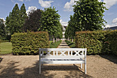 White garden bench in front of a row of trees, Borchers Garden, private garden in Goslar, Lower Saxony, Germany
