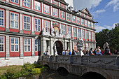 Entrance to Wolfenbüttel castle, now a secondary school, pupils sitting on the bridge, Wolfenbüttel, Lower Saxony, Germany