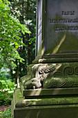 Ornamental gravestone amongst old trees in Wrisberg Garden, Wrisbergholzen, Lower Saxony, Germany