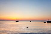 People bathing in sundown, Cefalú, Palermo, Sicily, Italy