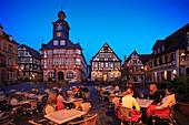 Restaurantgäste am abendlich erleuchteten Marktplatz, Rathaus und Marktbrunnen im Hintergrund Heppenheim, Hessische Bergstraße, Hessen, Deutschland