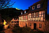 Blick über eine abendlich erleuchtete Gasse mit Fachwerkhäusern zur Starkenburg, Heppenheim, Hessische Bergstraße, Hessen, Deutschland