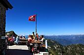 Rastende Wanderer vor Bergkulisse an der Hütte Capanna Tamaro, Bergwanderung zum Monte Tamaro, Tessin, Schweiz