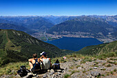 Hikers resting at the mountain top of Monte Tamaro, view to Lago Maggiore, hike in the mountains to Monte Tamaro, Ticino, Switzerland
