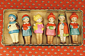 Handmade wooden figures in a cardboard box