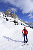 Woman backcountry skiing, ascending on a prepared track, Fanes-Sennes mountain range in the background,  Fanes-Sennes natural park, UNESCO World Heritage Site, Dolomites, South Tyrol, Italy