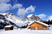 Snow-covered alpine huts with Dolomites summits in the background, Fanes-Sennes natural park, UNESCO World Heritage Site, Dolomites, South Tyrol, Italy