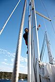 Sailor behind the mast of a sailing boat, Kornati archipelago, Croatia, Europe