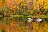 Two fisherman paddling canoe on Vermilion River