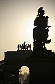Statue of Louis XIV with Arc de Triomphe du Carrousel in background in front of the Louvre Museum, Paris. France