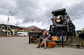 Tourists sitting in front of the historic steam locomotive, town of Jasper, Jasper National Park, Rocky Mountains, Alberta, Canada