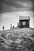 Children playing on the beach next to the hut of the Red Cross