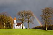 Kapelle mit Regenbogen im Alpenvorland, Oberbayern, Deutschland