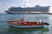 Fishing boat in harbor and cruiseship Caribbean Princess (Princess Cruises) at pier, Oranjestad, Aruba, Dutch Caribbean