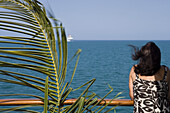 Palm Frond on Railing and Woman at railing aboard cruiseship MS Delphin (Hansa Kreuzfahrten), Caribbean Sea
