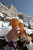 Two persons clinking wheat beer glasses, Alta Badia, Dolomites, Trentino-Alto Adige/Südtirol, Italy