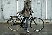 Aussen, Bluejeans, Draussen, Eine Person, Eins, Erwachsene, Erwachsener, Fahren, Fahrrad, Fahrräder, Fahrradfahren, Farbe, Frau, Frauen, Impuls, Jeans, Jugend, Jung, Mantel, Mäntel, Mensch, Menschen, Mode, Namenlos, Pedale, Profil, Profile, Radfahren, Sch