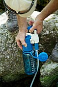 A hiker uses a water filtering system on Meader Ridge Trail during the spring months  Located in the White Mountains, New Hampshire USA  Note: